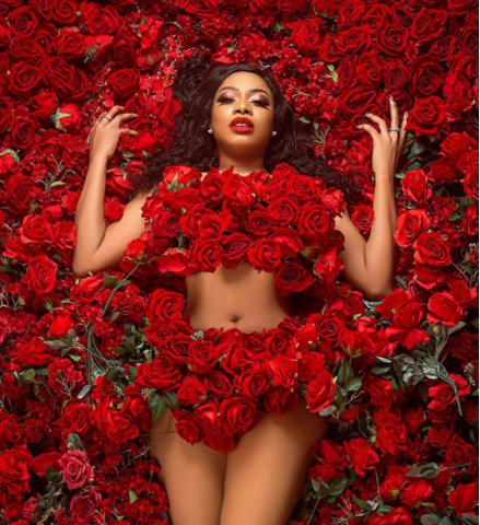 Chika Ike is clad in roses as she lays on a bed of roses