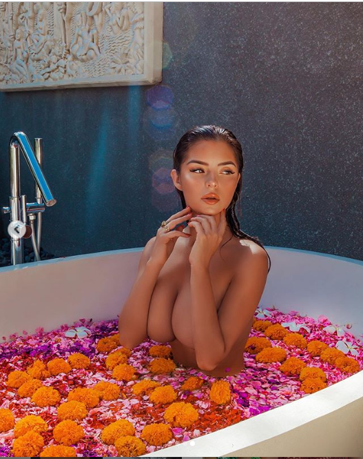 Demi Rose poses completely topless while soaking in a bath of flower petals (Photos)