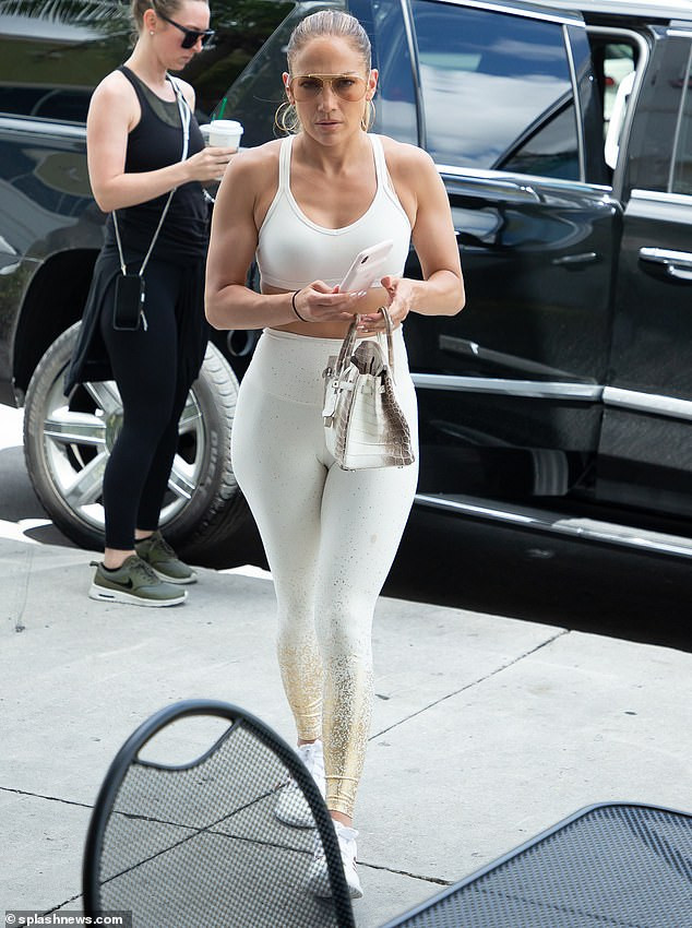 Jennifer Lopez showcases her backside in skintight white leggings and a sports bra (Photos)