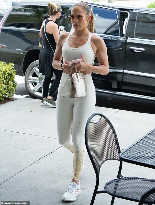 Jennifer Lopez showcases her backside in skintight white leggings and a sports bra (Photos)