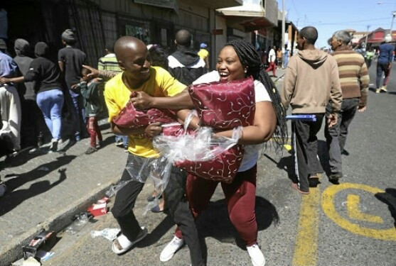 South African man and woman laughing gleefully as they leave with items looted from a foreigner