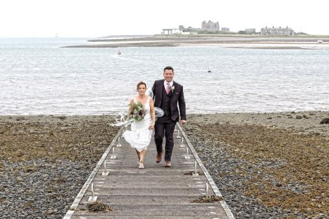 Bride, groom and wedding guests wear raincoats as they refuse to let rain spoil their big day