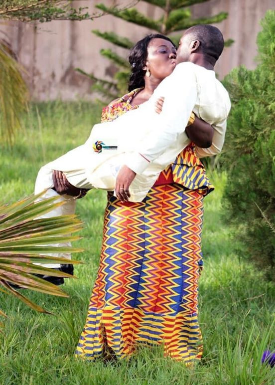 Trending photo of a Ghanaian bride carrying her husband while kissing him