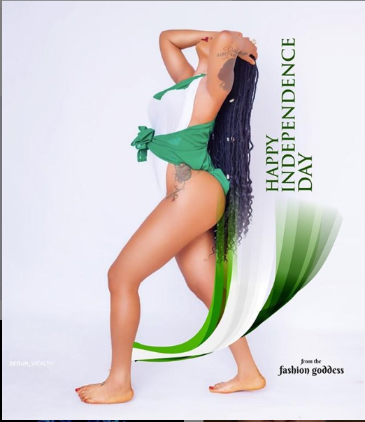 Toyin Lawani barely covers her body with a green and white piece of material to mark Nigeria