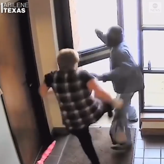 Elderly woman hailed after she was filmed bravely fighting off an armed bank robber (video)