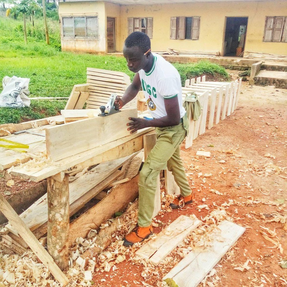 Nigerians commend Corps member who used his carpentry skill to construct desks for his students at no cost