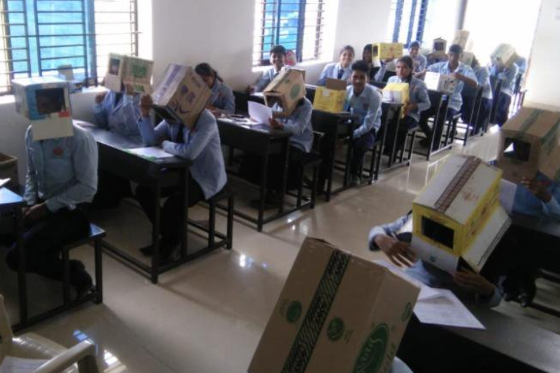 School apologises after photos of students wearing cardboard boxes on their heads during an exam goes viral