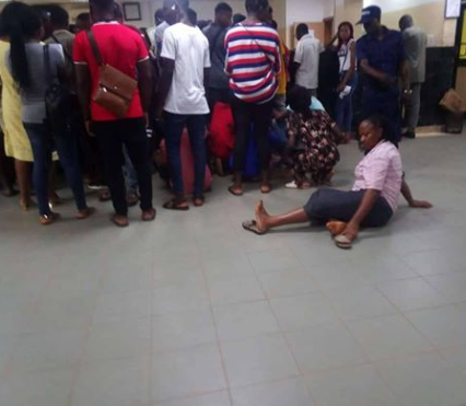 University students pictured sitting on the floor of a bank on campus due to lack of chairs for customers