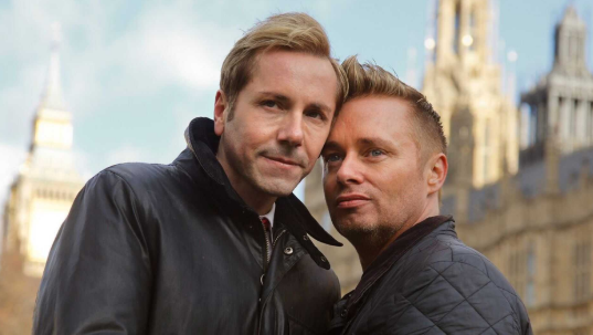 Daughter of Britain?s ?first gay dads? says she approves of one of her dads dating her ex-boyfriend