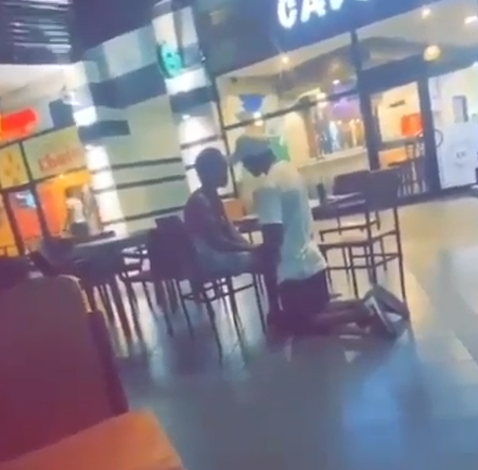 Man spotted kneeling down as he begs his girlfriend to forgive him in public (video)