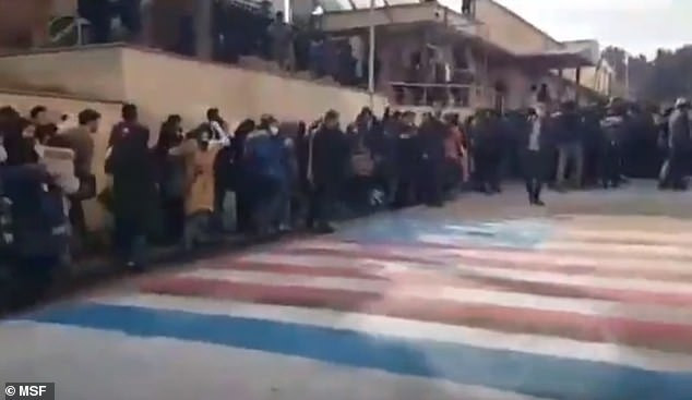 Incredible moment Iranian students refuse to step on US and Israeli flags amid anti-government protests across the country (video)