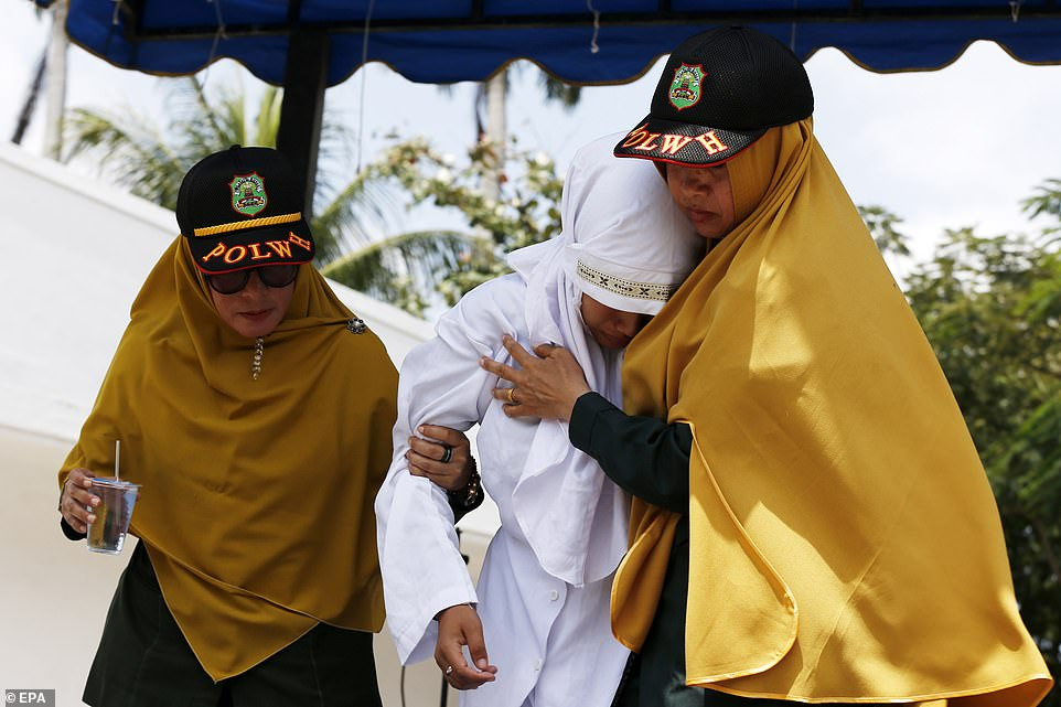 Indonesian woman is caned in public for having sex outside marriage (Photos)