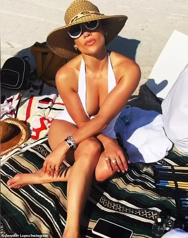 Jennifer Lopez, 50, flaunts her stunning figure in white swimsuit while relaxing on Miami beach (Photos)