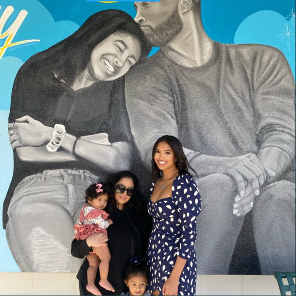 Vanessa Bryant and her daughters pose next to a mural of Kobe and Gigi Bryant
