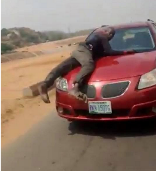 Policeman spotted on bonnet of speeding vehicle of lady who refused to stop for security operatives who were not wearing face masks (video)