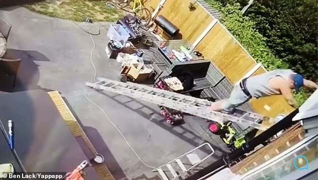 Painful moment man fell from the roof of a building after his ladder slipped (video)