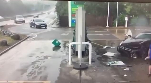 Video footage shows?dramatic moment?a black car?spins out of control before crashing into a petrol station