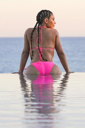 Kim Kardashain displays her curves in a skimpy pink bikini