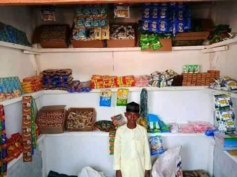 """Primary school pupil poses in front of his """"Shopping Complex"""" in Kano"""