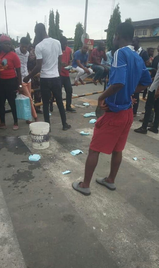 Aggrieved Rivers youths cook with firewood in front of Shell company as they protest sacking of their kinsmen