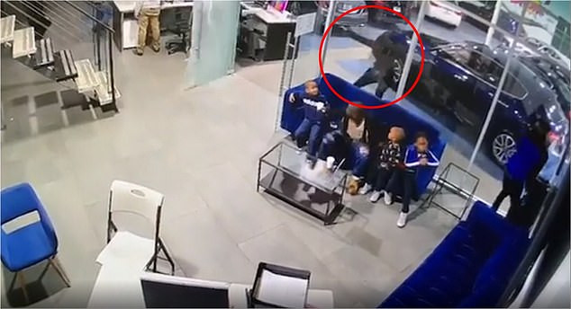 Shocking moment dad is shot as he shields his three kids from gunman who opened fire at car dealership in NYC (Video)