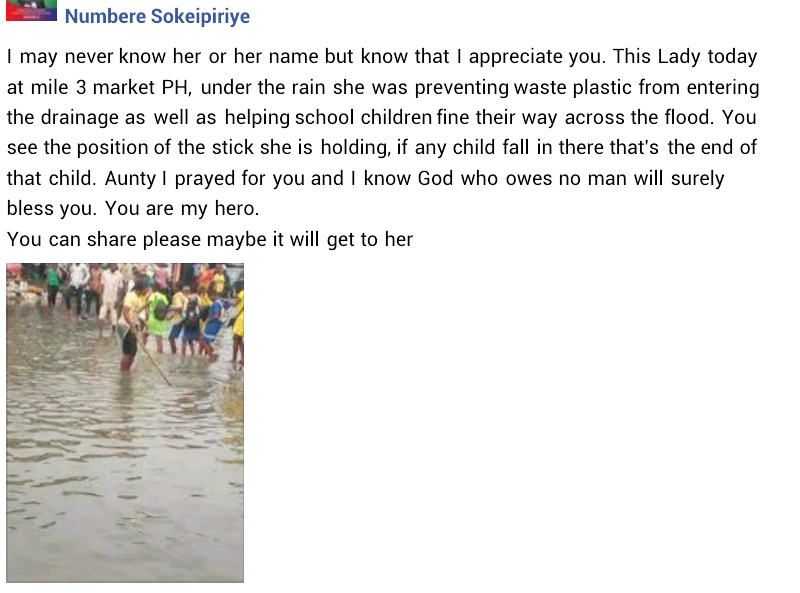 Lady spotted under the rain helping school children cross flooded market in Port Harcourt