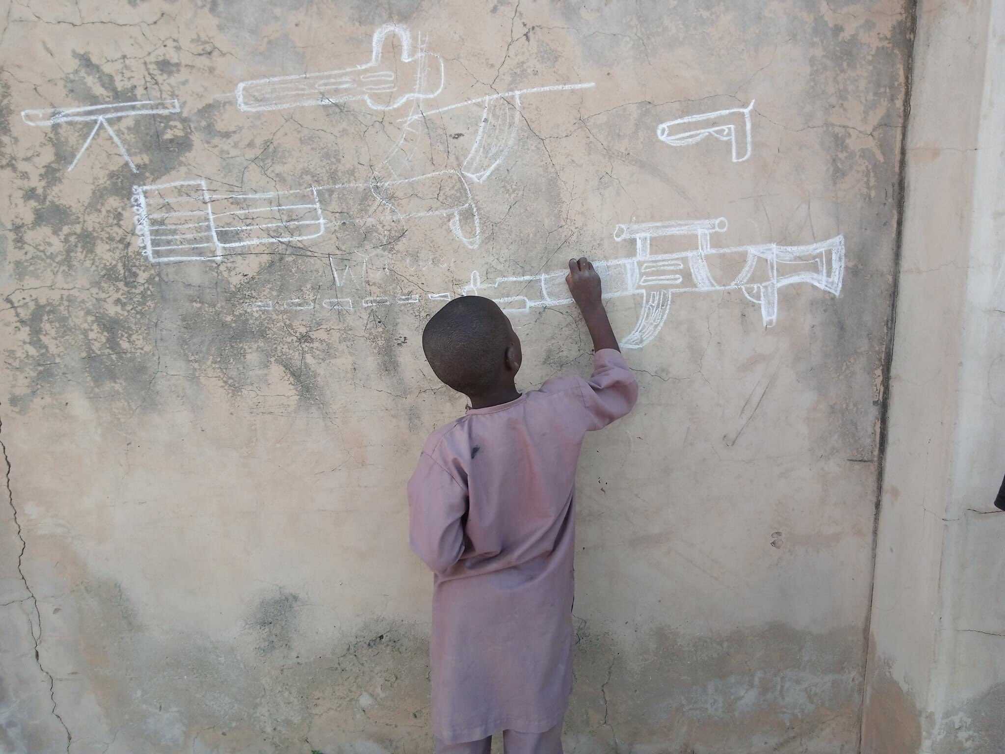 'This is sad' - Nigerians react to photo of little boy drawing a gun on the wall in Yobe