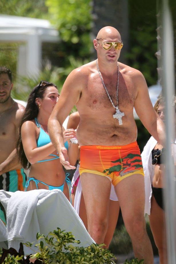 Bikini clad female fans rub oil on Tyson Fury