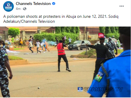 Photo of policeman shooting teargas at June12 protesters in Abuja