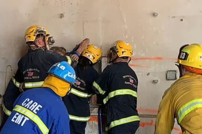 Naked woman trapped between two buildings left crying for help for half an hour before firefighters launched two-hour mission to free her