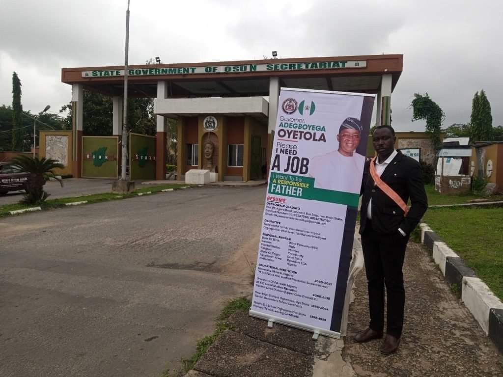 Man storms Osun secretariat with roll-up banner to beg Governor Oyetola for a job so he can be a responsible father