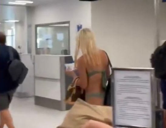 Moment woman strolls through airport in just a bikini and face mask