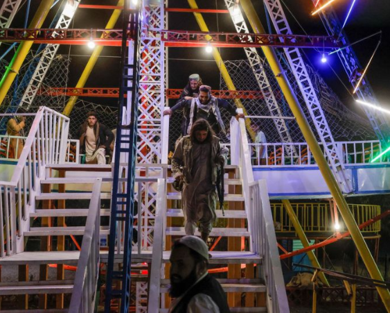 Taliban fighters frolic on amusement park rides and eat sweet while over 50 were killed in mosque bombing